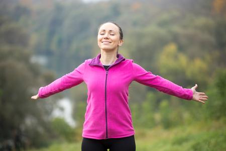 Ritratto di una giovane donna sorridente all'aperto in un abbigliamento sportivo, le mani tese, gli occhi chiusi. foto di concetto Archivio Fotografico