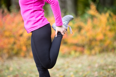 quadriceps: Warming up outdoors in the fall, stretching after or before running. Quadriceps standing. Closeup