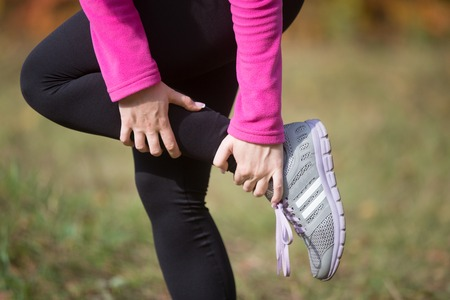 woman foot: Warming up outdoors in the autumn, holding an ankle, stretching after or before running. Concept photo