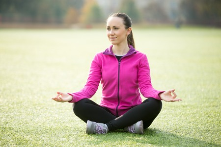 sukhasana: Sporty beautiful smiling young woman practicing yoga, sitting in Easy, Pleasant Posture, Sukhasana, meditating, working out outdoors on summer day wearing sportswear sweatshirt. Full length, side view Stock Photo