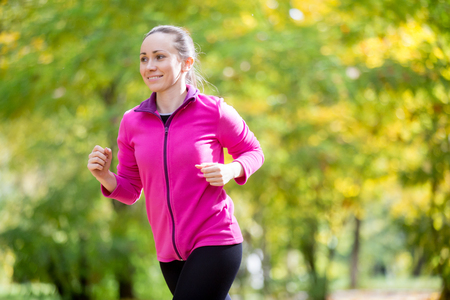 pace: Portrait of an attractive smiling woman jogging in the fall time. Concept photo Stock Photo