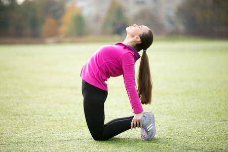 ushtrasana: Sporty beautiful smiling young woman practicing yoga, doing Ushtrasana, Camel posture, working out outdoors on summer day wearing sportswear sweatshirt. Full length, side view Stock Photo