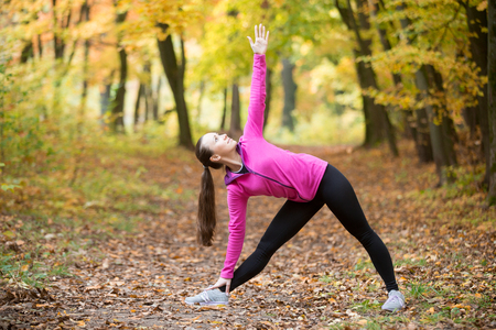utthita: Sporty beautiful young woman practicing yoga, standing in Utthita Trikonasana posture, Extended Triangle pose, working out outdoors on autumn day wearing sportswear sweatshirt. Full length, side view