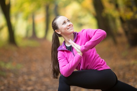 revolved: Sporty beautiful happy young woman practicing yoga, standing in Revolved Side Angle Posture, Parivrtta Parsvakonasana, working out outdoor on autumn day wearing sportswear sweatshirt. Closeup portrait