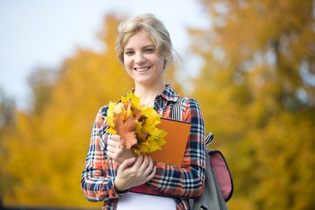 Portrait of smiling attractive female young student outdoors holding yellow maple leaves and copybooks, yellow background. Fall time. Back to school concept photo, looking at the camera