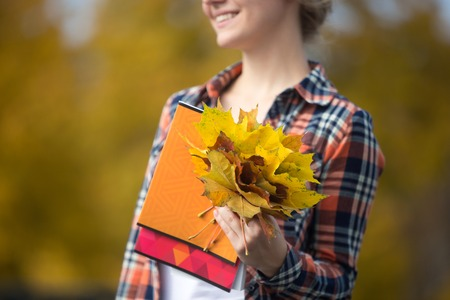 Smiling female young student outdoors holding yellow maple leaves, yellow background. Fall time. Back to school concept photo, closeup, horizontal