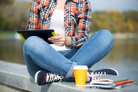 Student sitting turkish at bridge with tablet, copybook, coffee near, waterline behind. Back to school concept photo, closeup Stock Photo