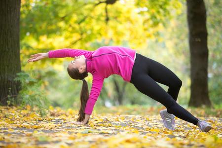Sportowa piękna młoda kobieta ćwiczy jogę, stoi w pozycji Camatkarasana, Wild Thing lub Flip-the-Dog, robi codzienną poranną rutynę, ćwicząc na świeżym powietrzu w jesienny dzień. Pełna długość