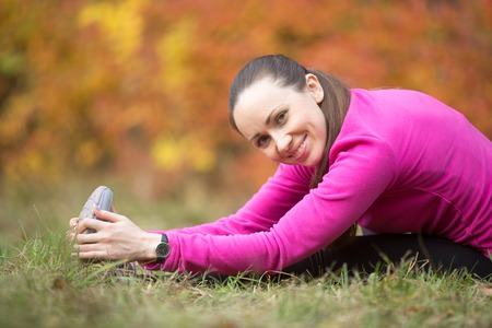 Portrait of sporty young woman practicing yoga, doing seated Hamstring Stretch, paschimothanasana, stretching before running routine, looking at camera and smiling, working out outdoors on autumn day