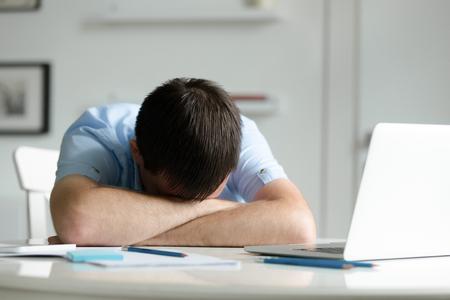 Retrato de un hombre acostado en el escritorio cerca de la computadora portátil, la cabeza en sus manos cruzadas, educación, foto de concepto de negocio. Estilo de vida Foto de archivo