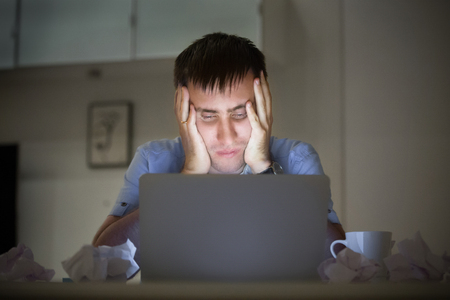 Portrait of a man grabbing his head in despair at the desk near the laptop, late at night. Education, business concept photo. Lifestyle 版權商用圖片