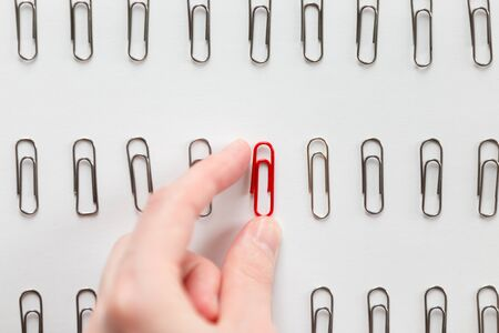 lay forward: Hand picking among metal paperclips one red, different from the others, isolated on white background. Stand out from the crowd concept, high angle