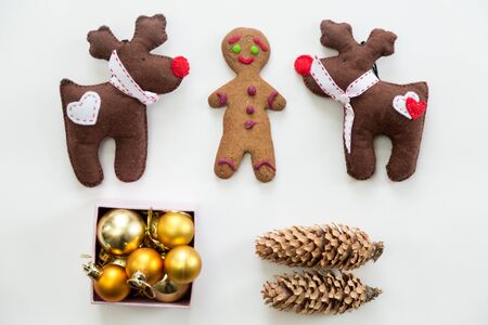 nosed: Flat view of cute Christmas decoration, cones, box of glass balls, ginger man, Rudolph the Red Nosed Reindeer toys. Christmas concept, high angle