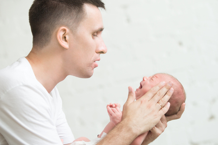 Portrait of a young man soothing a screaming newborn. Family , healthy birth concept photo