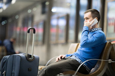 Portrait of young handsome man wearing casual style clothes sitting on the bench in modern airport using smartphone. Passenger travelling with luggage bag making call, while waiting for his flight