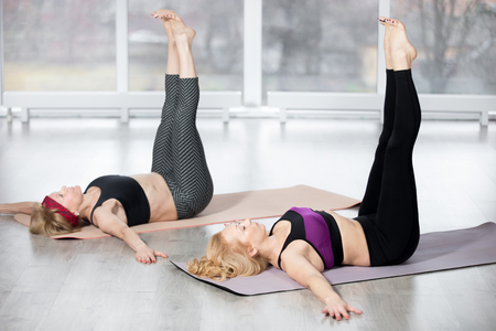 Fitness, stretching practice, group of two attractive fit mature women working out in sports club, warming up, doing Double Straight Leg Lift, exercise for upper and lower abdominals, full length