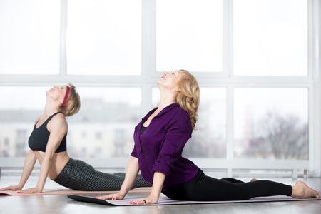 Fitness, práctica de estiramiento, grupo de dos atractivas mujeres maduras en forma feliz en ropa deportiva trabajando en un club deportivo, haciendo la postura de Cobra, ejercicio de flexión hacia atrás, bhudjangasana (Bhujangasana) en clase