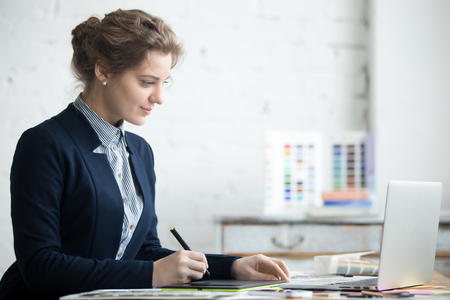 Portrait of beautiful happy young graphic designer woman working at home office desk. Attractive model wearing suit using digital tablet, sitting in front of laptop. Interior shot
