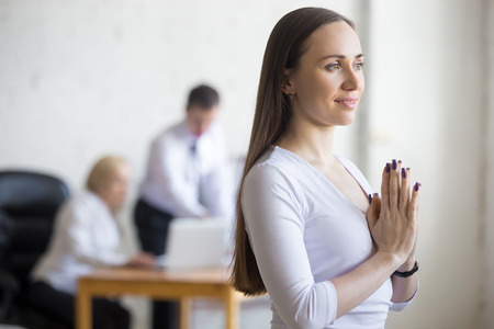 stress relief: Business and healthy lifestyle concept. Portrait of beautiful sporty cheerful young office woman standing in yoga pose at workplace. Model using stress relief techniques at work