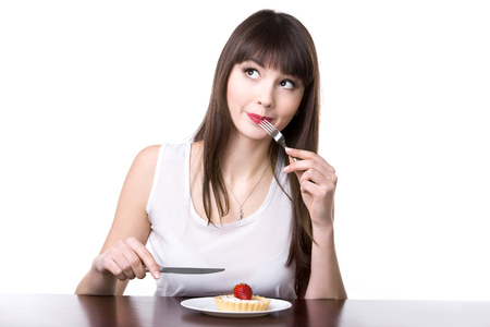 Young playful happy woman sitting in front of plate with delicious strawberry tart cake in dough basket, holding knife and fork, deciding to try sweet dessert, studio, white background, isolated Banque d'images