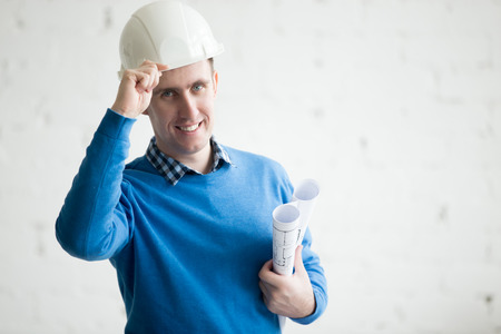 Portrait of young cheerful handsome engineer in white hard hat holding drawings, standing in architectural agency. Friendly smiling attractive Caucasian model posing with project plans, copy space