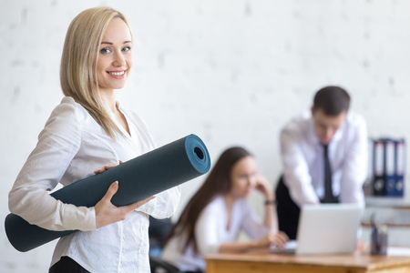 Business and healthy lifestyle concept. Beautiful sporty young office woman finished her work and going at fitness training. Cheerful model posing with exercise mat and friendly smiling at camera Stok Fotoğraf
