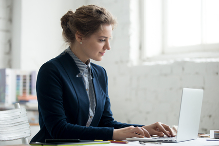 Portrait of beautiful young designer woman working on new design project on laptop at office desk. Attractive model in suit using computer, typing. Interior shot Stock fotó