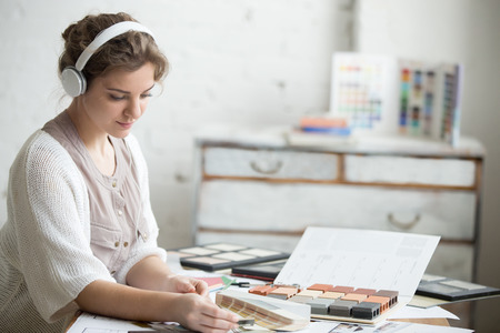 Portrait of beautiful happy young designer woman sitting in headphones at home office desk in design agency, working in loft interior. Attractive model choosing materials for new project. Indoors