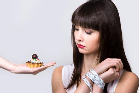 Junge Diätfrau, die vor köstlichem Sahnetorte mit den mit Maßband gefesselten Händen sitzt und verbotenes Essen mit Sehnsucht und hungrigem Ausdruck betrachtet, Studio, grauer Hintergrund, isoliert