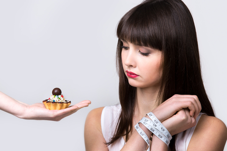 Young dieting woman sitting in front of delicious cream tart cake with hands tied with measuring tape, looking at forbidden food with longing and hungry expression, studio, gray background, isolated