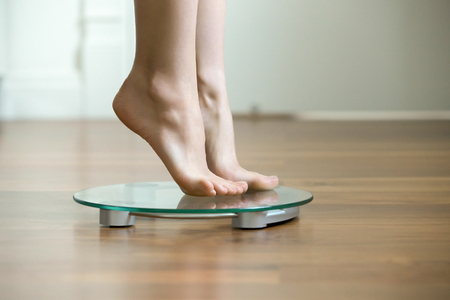 Female on tiptoes standing on glass floor weight scales, closeup