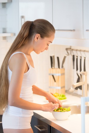 Young woman with long braid standing at the kitchen and making green salad, wearing underwear panties and white color tank top. Lifestyle