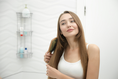 Portrait of a young smiling girl brushing her long hair, looking at the bathroom mirror. Lifestyle, beauty concept photo