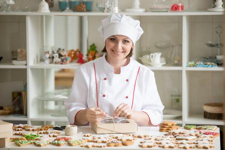 Professionelle, freundliche, lächelnde Konditorin, die eine Schachtel mit Keksen einwickelt, Winterweihnachtssortiment auf dem Tisch. Blick in die Kamera