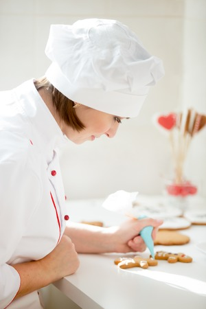 Professional female confectioner bent decorating a gingerman with icing sugar using a pastry bag, preparing for Christmas. Lifestyle, vertical, Christmas concept photo