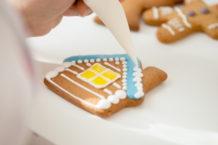 Close up of confectioner hand decorating a gingerbread house, the roof with icing sugar for a snowy effect using a pastry bag. View over a shoulder, lifestyle Zdjęcie Seryjne