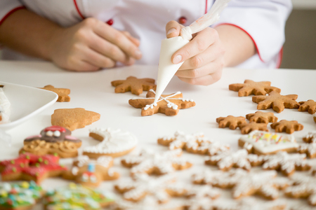Close up of female confectioner hands decorating gingerbread stars with icing sugar using selfmade pastry bag making cutest Christmas cookies