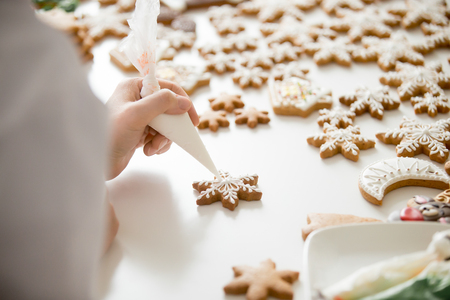 Close up of female confectioner hands decorating gingerbread stars with icing sugar using selfmade pastry bag, making decorative gingerbread ornaments