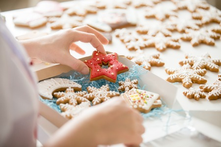 Close up of confectioner hand packing an amazing traditional Christmas gingerbread cookies into a cardboard box. Christmas concept photo, lifestyle