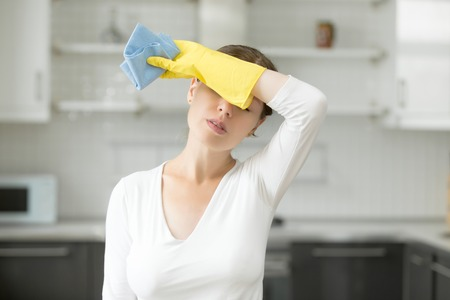 Tired and exhausted woman, frustrated with doing much work about the house resting for a minute or wiping her forehead after finishing work. Home, housekeeping concept Stock Photo