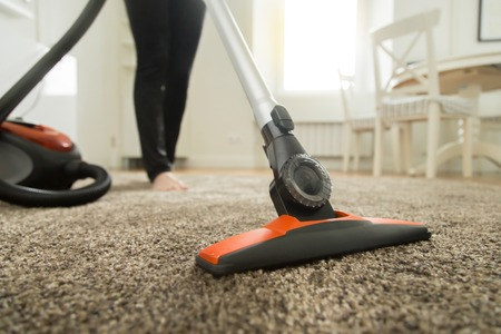 chores: Close up of the vacuum cleaner, focus on the brush, woman cleaning the carpet. Home, housekeeping concept Stock Photo