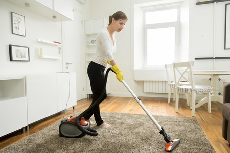 tidying: Woman in casual wear vacuum cleaning the carpet, tidying white modern living room. Home, housekeeping concept