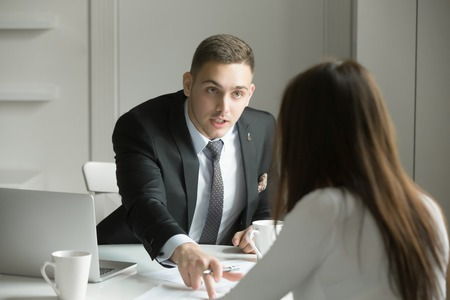 Young handsome businessman is pointing to a mistake in a paper, incorrectly done task by a woman or she is missing deadlines, showing his authority. Business concept photo