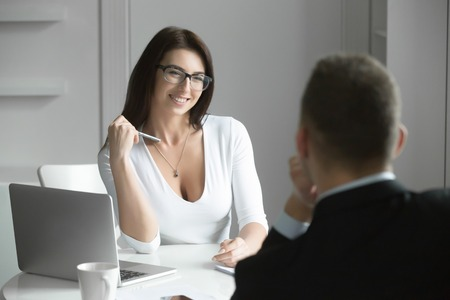 Joven sonriente hermosa mujer de negocios hablando a un solicitante de empleo masculino en el mostrador, entrevistando a coquetear con un compañero de trabajo. Vista trasera de un hombre. Concepto de negocio foto Foto de archivo - 65966489