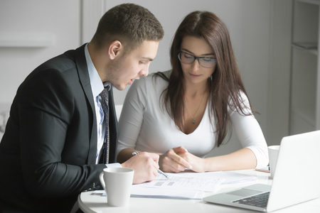 business performance: Businessman and businesswoman at office desk, working together, man instructing and coaching woman to give her an opportunity to grow and achieve optimal performance. Business concept photo