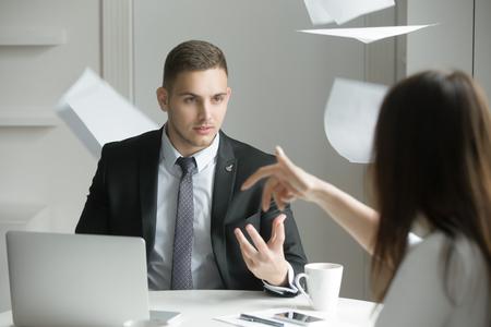 Twee mensen uit het bedrijfsleven tijdens een verhitte geschil of argument, het proces van onderhandelingen afbreekt, misverstanden, geen overeenstemming kan worden bereikt. Vrouw is het gooien van papieren. Business concept foto