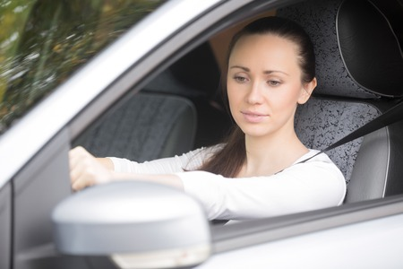 drivers seat: Woman buckling a seat belt in the drivers seat, safety belt, to secure against harmful movement during a collision or a sudden stop Stock Photo
