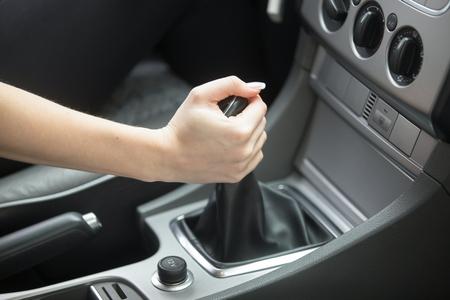 Close-up di mano femminile audio del veicolo messa a punto per fornire intrattenimento in auto o ottenere informazioni, rendendo il volume del suono più forte