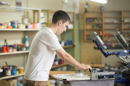 Jonge zelfverzekerde, ervaren man werkt met wisser in een kleine fabriek, knappe werkman met behulp van grafiekgereedschappen, zeefdruk op kledingstoftechniek