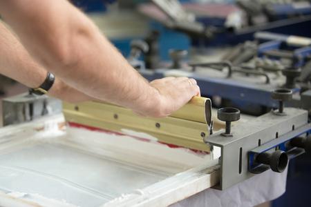 Nahaufnahme der männlichen Hände traditionellen Rakel zu erforschen, um ein Bild auf weißem Stoff Kleidung Schaffung von Tinte durch ein Sieb mit Bereichen Pressen blockiert durch eine Schablone aus Standard-Bild
